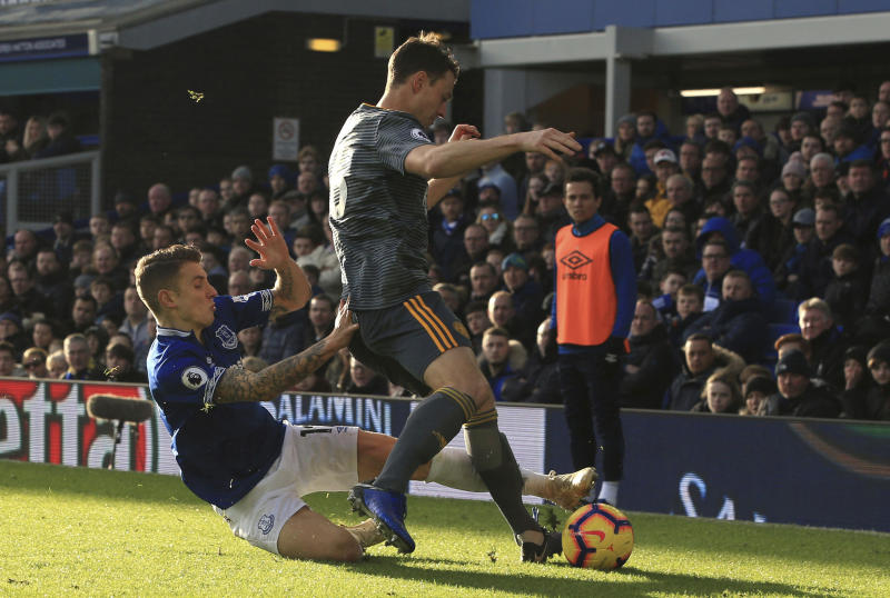 Everton's Lucas Digne, left, tries to reach the ball, around the legs of Leicester City's Jonny Evans during their English Premier League soccer match at Goodison Park in Liverpool, England, Tuesday Jan. 1, 2019. (Peter Byrne/PA via AP)