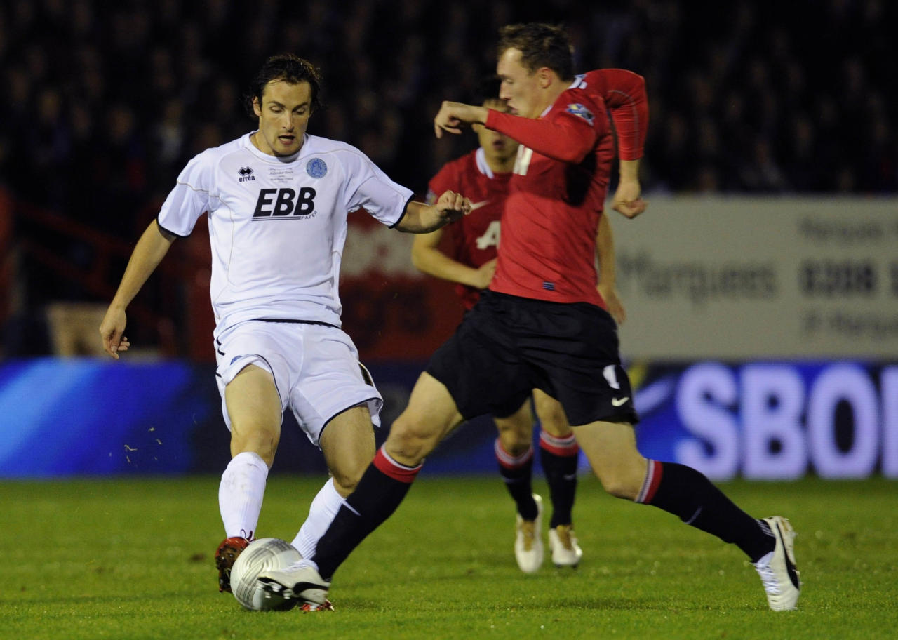 Aldershot Town's Danny Hylton, left, is tackled by Manchester United''s Phil Jones during their English League Cup soccer match at the EBB stadium, Aldershot, Tuesday, Oct. 25, 2011. (AP Photo/Tom Hevezi)