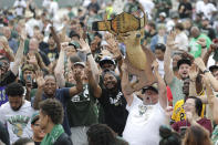 Kirk Carley, of Milwaukee, right, holds up a deer statue during a parade celebrating the Milwaukee Bucks' NBA Championship basketball team Thursday, July 22, 2021, in Milwaukee. (AP Photo/Aaron Gash)