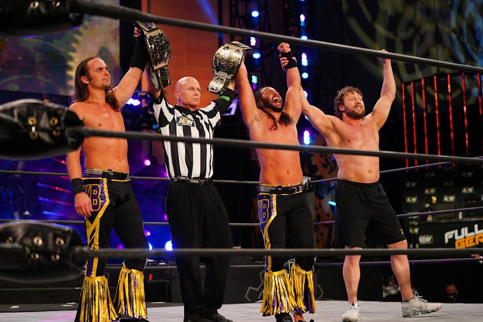 The Young Bucks celebrate with Kenny Omega after winning the AEW Tag Team Championship at 'Full Gear' on November 7. (Photo Credit: AEW)
