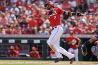 Cincinnati Reds' Nick Castellanos hits an RBI-double during the first inning of a baseball game against the Colorado Rockies in Cincinnati, Saturday, June 12, 2021. (AP Photo/Aaron Doster)