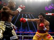 Floyd Mayweather, Jr. of the U.S. (L) and Manny Pacquiao of the Philippines fight in the first round of their welterweight WBO, WBC and WBA (Super) title fight in Las Vegas, Nevada, May 2, 2015. REUTERS/Steve Marcus