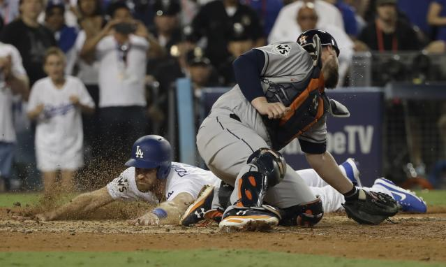 <p>Los Angeles Dodgers' Logan Forsythe scores past Houston Astros catcher Brian McCann during the 10th inning of Game 2 of baseball's World Series Wednesday, Oct. 25, 2017, in Los Angeles. Forsythe scored from second on a hit by Enrique Hernandez. (AP Photo/David J. Phillip) </p>