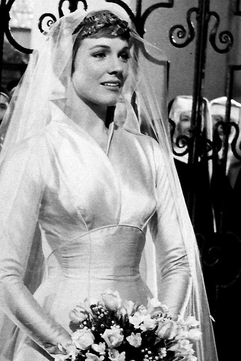 <p>For the first half of <em>The</em> <em>Sound of Music</em><em>,</em> we see Maria, played by Julie Andrews, only in her uniform. But we're treated to an elegant structured satin gown, elaborate headpiece, and simple veil in the second half when her sisters give her away to Captain Von Trapp.</p>