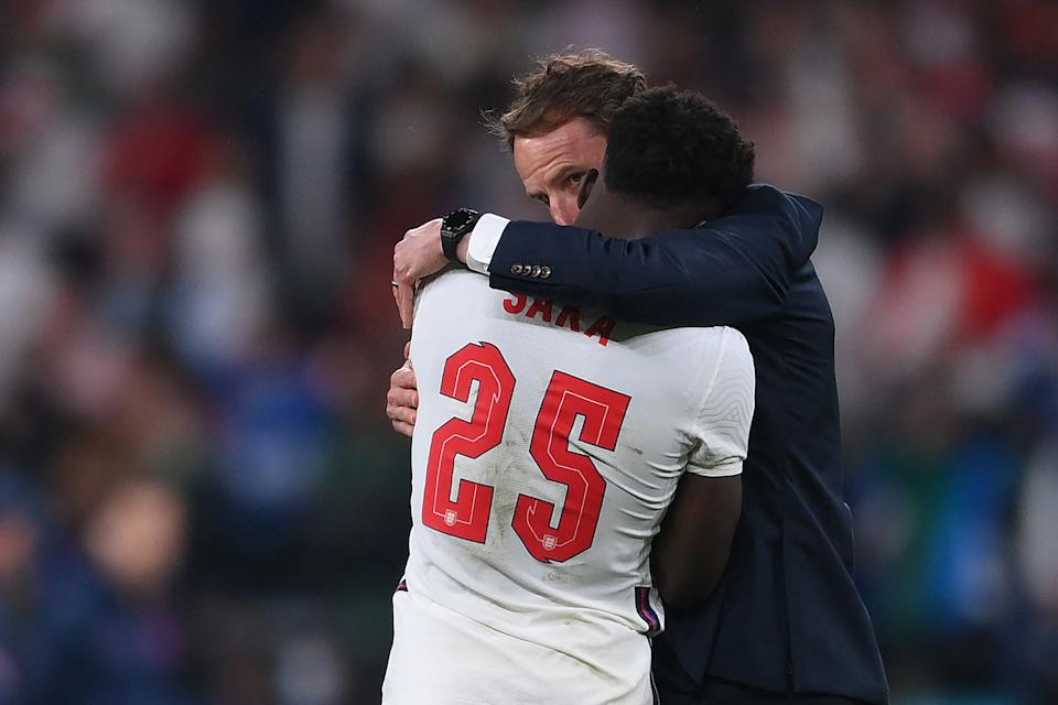 England's coach Gareth Southgate speaks to England's midfielder Bukayo Saka after their loss in the UEFA EURO 2020 final football match between Italy and England at the Wembley Stadium in London on July 11, 2021. (Photo by Laurence Griffiths / POOL / AFP) (Photo by LAURENCE GRIFFITHS/POOL/AFP via Getty Images)