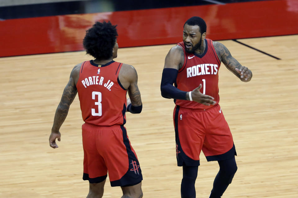 Houston Rockets guard Kevin Porter Jr. (3) and guard John Wall (1) celebrate after Wall scored in the final minute of the team's NBA basketball game against the Dallas Mavericks on Wednesday, April 7, 2021, in Houston. (AP Photo/Michael Wyke, Pool)
