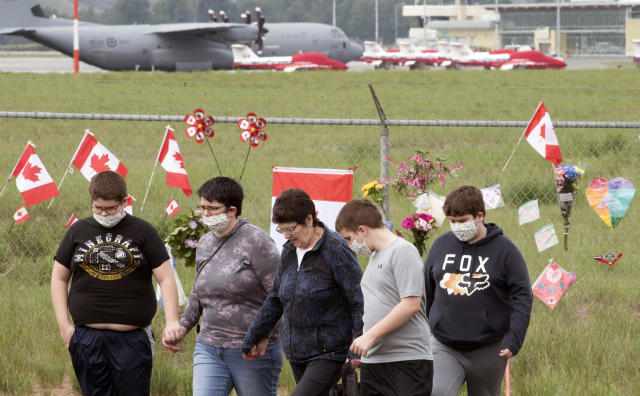 The Canadian Forces Snowbirds jets are seen in the background as a family pays their respects at the Kamloops airport in Kamloops, British Columbia, Monday, May 18, 2020. Capt. Jennifer Casey died Sunday after the Snowbirds jet she was in crashed shortly after takeoff. The pilot of the aircraft is in hospital with serious injuries. (Jonathan Hayward/The Canadian Press via AP)