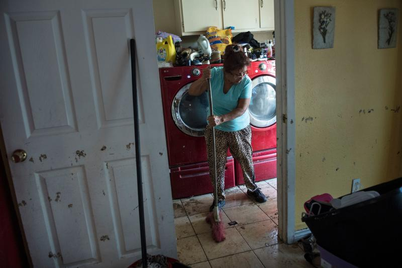 A woman cleans the floors of a once flooded house in Houston. (BRENDAN SMIALOWSKI/AFP/Getty Images)