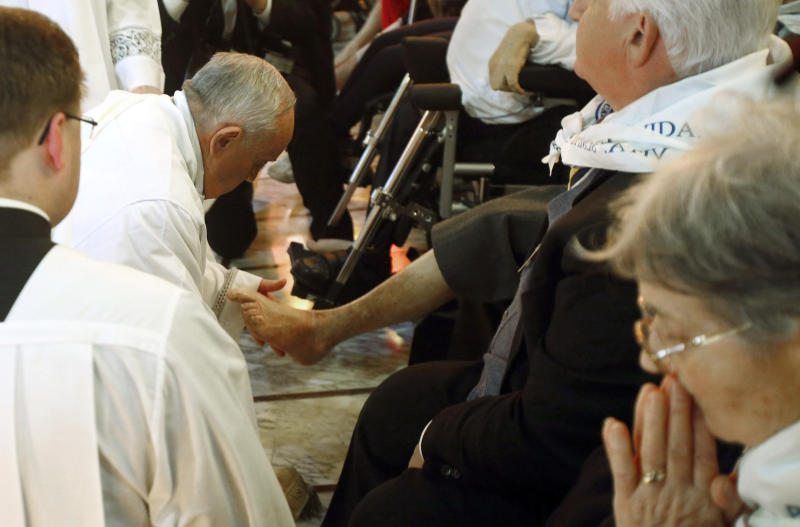 """Pope Francis kneels to wash the foot of a man at the Don Gnocchi Foundation Center in Rome, Thursday, April 17, 2014. The Pontiff has washed the feet of 12 elderly and disabled people — women and non-Catholics among them — in a pre-Easter ritual designed to show his willingness to serve like a """"slave."""" Francis' decision in 2013 to perform the Holy Thursday ritual on women and Muslim inmates at a juvenile detention center just two weeks after his election helped define his rule-breaking papacy. It riled traditionalist Catholics, who pointed to the Vatican's own regulations that the ritual be performed only on men since Jesus' 12 apostles were men. The 2014 edition brought Francis to a center for the elderly and disabled Thursday. Francis kneeled down, washed, dried and kissed the feet of a dozen people, some in wheelchairs. He said the ritual is a gesture of """"a slave's service."""" (AP Photo/Riccardo De Luca)"""
