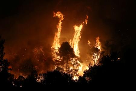 Flames rise as a wildfire burns near the village of Makrimalli, on the island of Evia