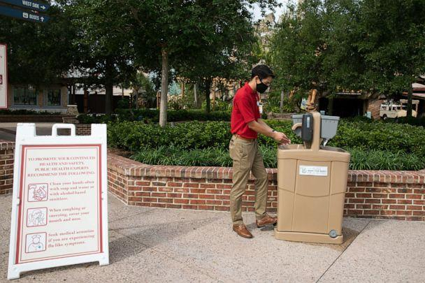 Prior to the May 20, 2020, reopening of Disney Springs a Disney cast member cleans his hands using a new hand-washing station installed at the shopping, dining and entertainment district. (Olga Thompson, photographer)