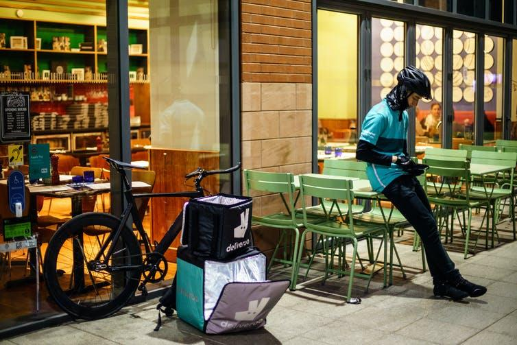 A Deliveroo delivery cyclist waits outside of a restaurant