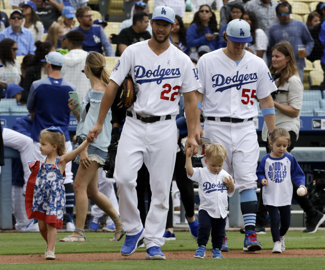 As part of a Father's Day celebration, Los Angeles Dodgers starting pitcher Clayton Kershaw (22) and relief pitcher Tom Koehler walk onto the field with their children before a baseball game against the San Francisco Giants in Los Angeles, Sunday, June 17, 2018. (AP Photo/Chris Carlson)