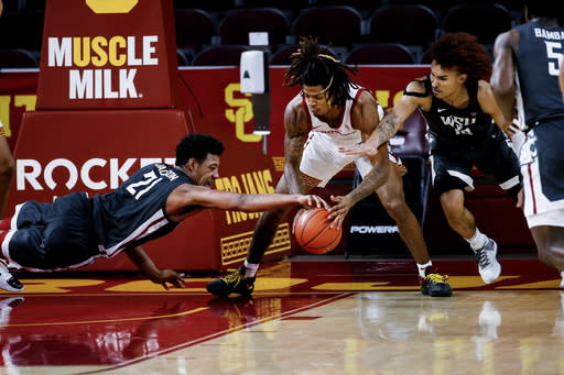 Southern California guard Isaiah White, center, and Washington State center Dishon Jackson, left, and guard Isaac Bonton reach for the ball during the second half of an NCAA college basketball game Saturday, Jan. 16, 2021, in Los Angeles. (AP Photo/Ringo H.W. Chiu)