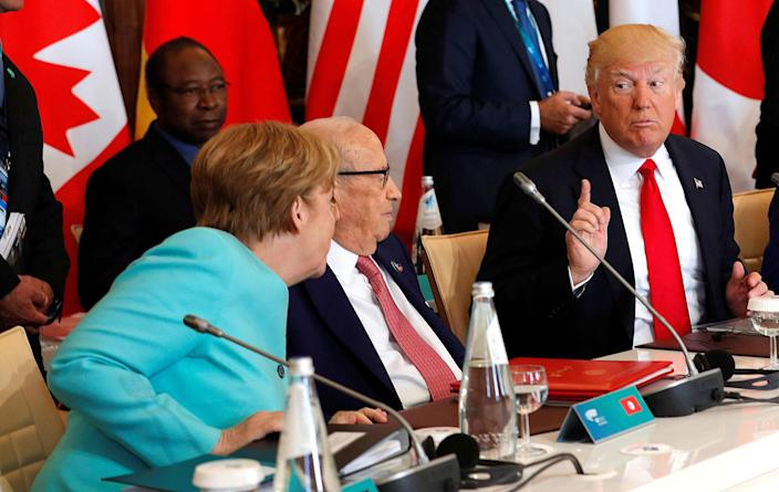<p>German Chancellor Angela Merkel (L) sits next to Tunisia's President Beji Caid Essebsi (C) and speaks to U.S. President Donald Trump (R) as they attend a G7 expanded session during the G7 Summit in Taormina, Sicily, Italy, May 27, 2017. (Photo: Philippe Wojazer/Reuters) </p>