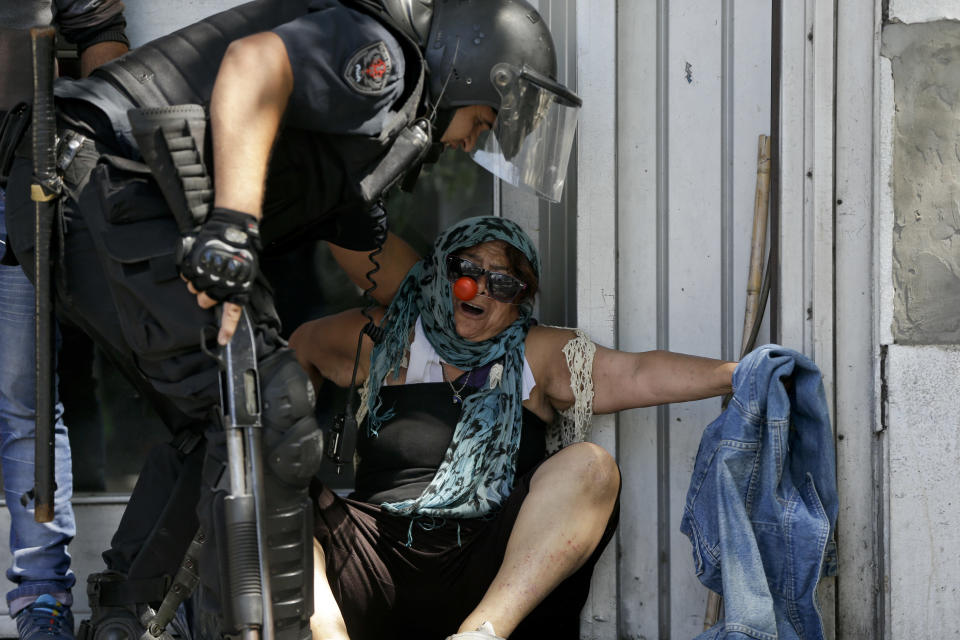 <p>A police officer helps a demonstrator remove herself from clashes during a general strike against a pension reform measure outside Congress in Buenos Aires, Argentina, Monday, Dec. 18, 2017. Union leaders complain the legislation, which already passed in the Senate, would cut pension and retirement payments as well as aid for some of poor families. (AP Photo/Natacha Pisarenko) </p>