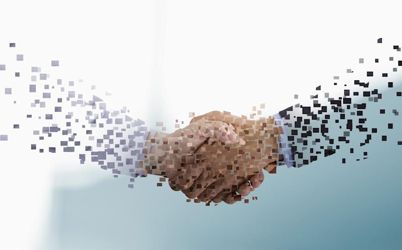 Pixels forming arms of businessmen shaking hands
