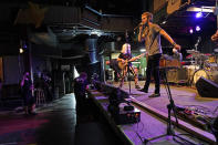 """In this Oct. 26, 2020, photo, David Shaw, foreground, frontman for the band The Revivalists, performs with actor Harry Shearer, co-author and character in the movie """"This Is Spinal Tap,"""" as they record a video stream concert with the band Galactic, inside an empty Tipitina's music club, in New Orleans. Music clubs all over the nation — pop culture icons like the Troubadour in West Hollywood, the Bluebird Cafe in Nashville, The Bitter End in New York's Greenwich Village — are shuttered due to the coronavirus. And owners fear for the future of their businesses and of a musical way of life. (AP Photo/Gerald Herbert)"""