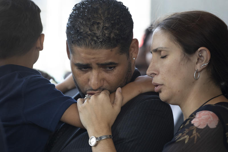 """Juan Rodriguez, holding his son Tristan, leaves Bronx Criminal Court with his wife Marissa after a hearing, Thursday, Aug. 1, 2019 in New York. The New York father has pleaded not guilty to manslaughter and other charges in the deaths of their 1-year-old twins left in a car on Friday while he put in a day at work. Prosecutors say Rodriguez told police he thought he had dropped the twins off at day care. They say he told police """"I blanked out. My babies are dead. I killed my babies."""" (AP Photo/Mark Lennihan)"""