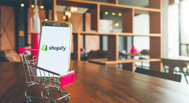 Image of a shopping cart toy on a wooden desk carrying a mobile phone that features the Shopy (SHOP) logo on it (growth stocks to buy)