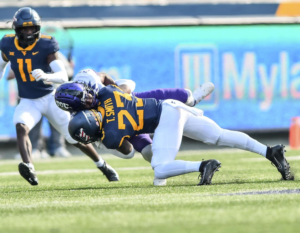 West Virginia safety Tykee Smith (23) makes a tackle against TCU during the first half of an NCAA college football game on Saturday, Nov. 14, 2020, in Morgantown, W.Va. (William Wotring/The Dominion-Post via AP)