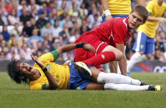 Brazil's Neymar(L) reacts to falling with Belarus' Igor Kuzmenok during their men's Group C football match at the London 2012 Olympic Games at Old Trafford in Manchester July 29, 2012. REUTERS/Andrea Comas (BRITAIN - Tags: SPORT SOCCER SPORT OLYMPICS)