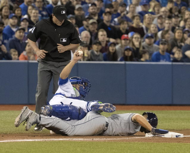 Tampa Bay Rays' Austin Meadows tumbles face down into third base after being tagged out in a run-down by Toronto Blue Jays catcher Luke Maile during the sixth inning of a baseball game in Toronto on Saturday, April 13, 2019. (Fred Thornhill/The Canadian Press via AP)