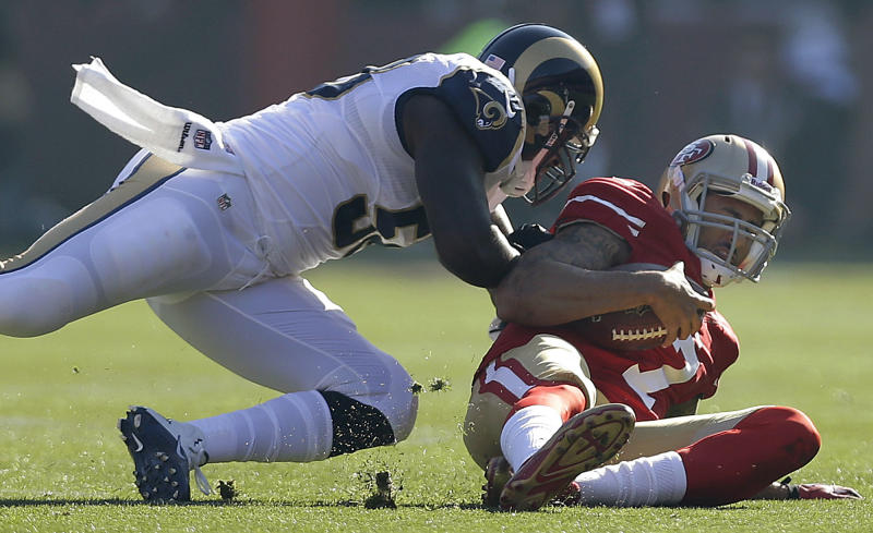 San Francisco 49ers quarterback Colin Kaepernick, right, is hit by St. Louis Rams outside linebacker Jo-Lonn Dunbar as he slides to the ground during the first quarter of an NFL football game in San Francisco, Sunday, Dec. 1, 2013. Dunbar was penalized for a personal foul on the play. (AP Photo/Marcio Jose Sanchez)