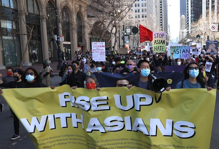 Protesters hold signs as they march along Market Street before a rally to show solidarity with Asian Americans at Embarcadero Plaza on March 26, 2021 in San Francisco, California. Hundreds of people marched through downtown San Francisco and held a rally at Embarcadero Plaza in solidarity with Asian Americans who have recently been the targets of hate crimes across the United States. (Photo by Justin Sullivan/Getty Images)