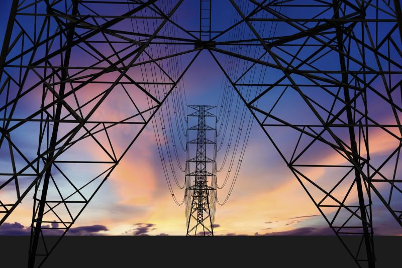 Towers carrying power lines near dawn or dusk.