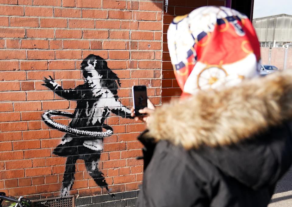 Nottingham resident Paris Hendrix takes a photograph of graffiti artwork, now confirmed to be the work of street artists Banksy, on a side of a property at Rothesay AVenue and Ilkeston Road, Nottingham. The artwork depicts a young girl playing with a tyre and is painted on a wall near to an abandoned bicycle that is missing a wheel.