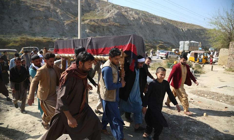 A group of Afghan pallbearers carry a coffin covered in a drape across rough ground with a line of mountains in the background