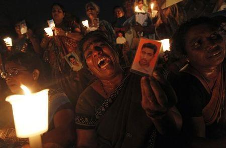 A Tamil woman cries as she holds up an image of her family member who disappeared during the civil war with the LTTE at a vigil to commemorate the international day of the disappeared in Colombo