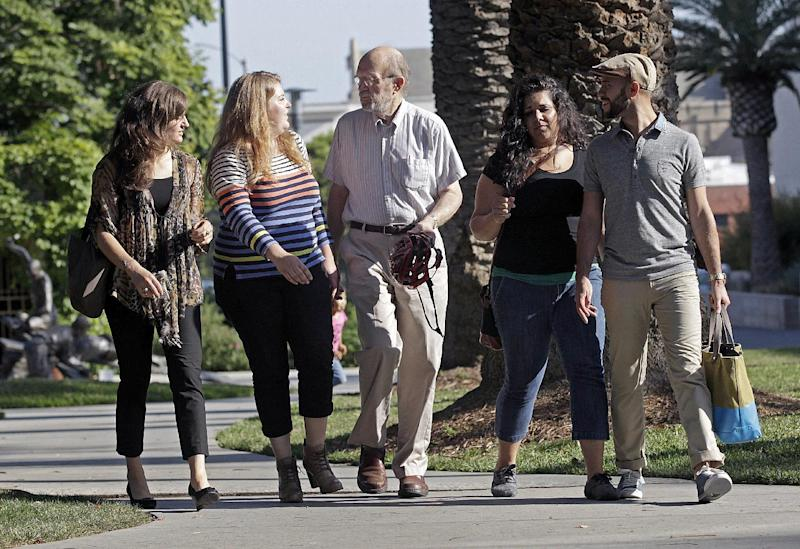 In this Wednesday, June 12, 2013 photo, straight and gay members of OneTable, from left, Samantha Curley, Chelsea McInturff, faculty adviser Glen Stassen, Marissa Nunes and Nick Palacios walk on the campus of the Fuller Theological Seminary in Pasadena, Calif. Fuller, the largest multi-denominational seminary in the world, became the first such school to sanction an official student organization - OneTable - for gay, lesbian, bisexual and transgendered students earlier this year. Attempts to start unofficial gay student groups at other seminiaries throughout the country have been met with censorship and outright bans. Though the group's approval is seen by many as progress, some argue it's a step forward with strings attached. (AP Photo/Reed Saxon)