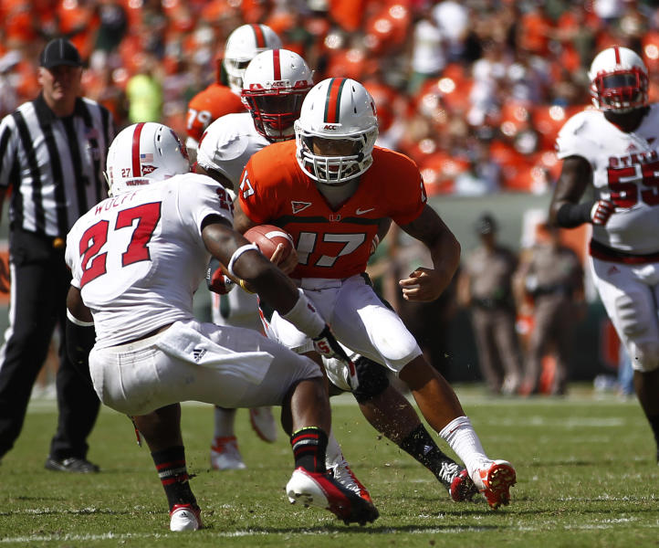 Miami quarterback Stephen Norris is stopped by North Carolina State's Earl Wolff (27) during the second half of an NCAA college football game in Miami, Saturday, Sept. 29, 2012. Miami won 44-37. (AP Photo/J Pat Carter)