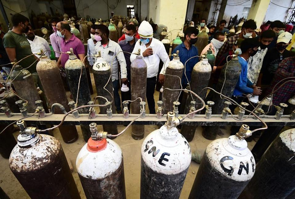 People refill medical oxygen cylinders for Covid patients at an oxygen refill station in Allahabad, 20 April