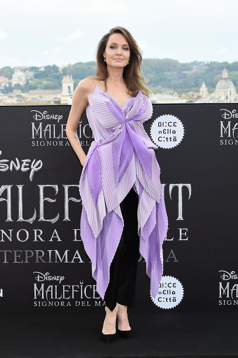 The actress wears layered, purple top by Givenchy with a pair of black trousers and matching heels. <em>[Photo: Getty]</em>