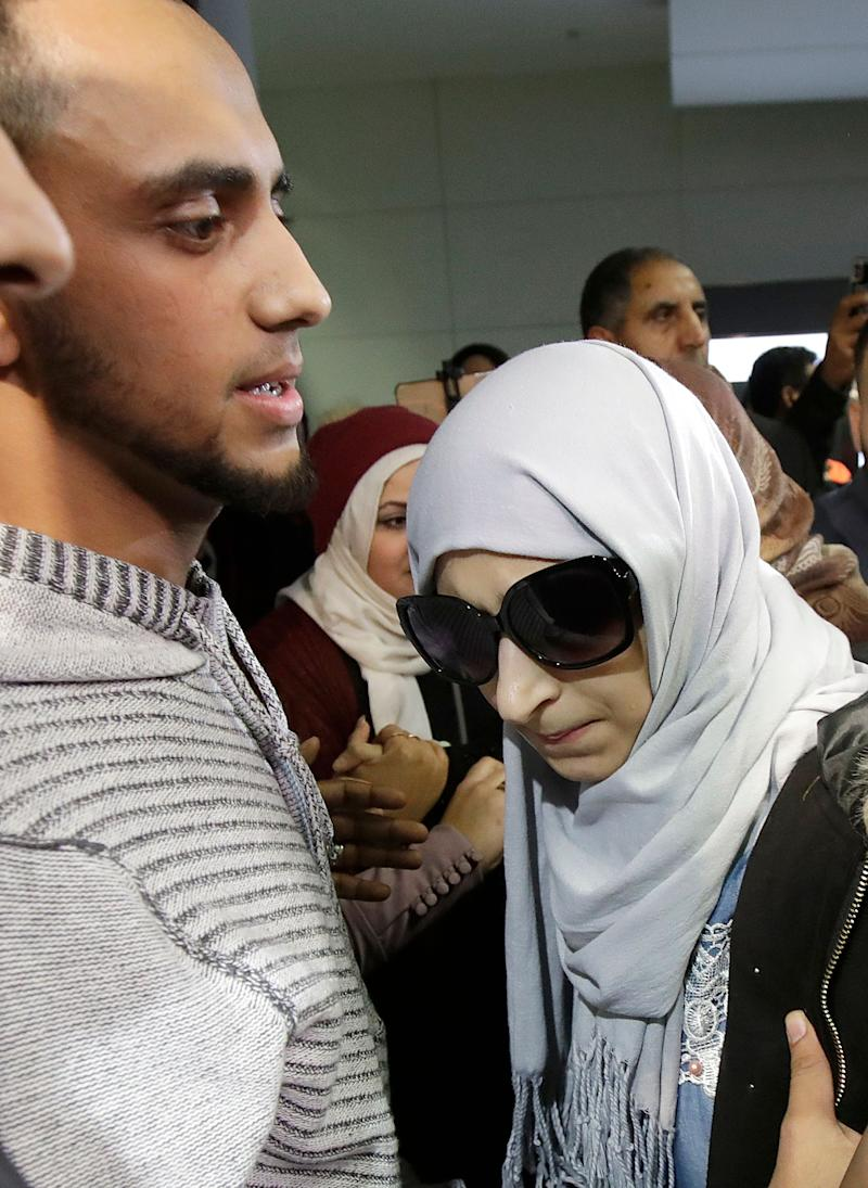 Shaima Swileh, right, stands with her husband Ali Hassan after Swileh arrived at San Francisco International Airport in San Francisco, Wednesday, Dec. 19, 2018. Swileh is the Yemeni mother who won her fight for a waiver from the Trump administration's travel ban that would allow her to go to California to see her dying 2-year-old son.