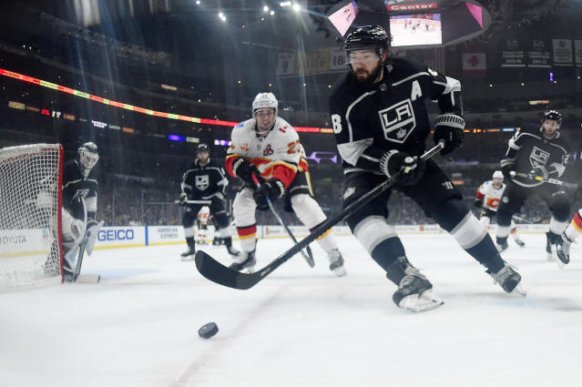 Los Angeles Kings defenseman Drew Doughty, second from right, moves the puck while under pressure from Calgary Flames center Sean Monahan during the third period of an NHL hockey game Thursday, Feb. 13, 2020, in Los Angeles. The Kings won 5-3. (AP Photo/Mark J. Terrill)