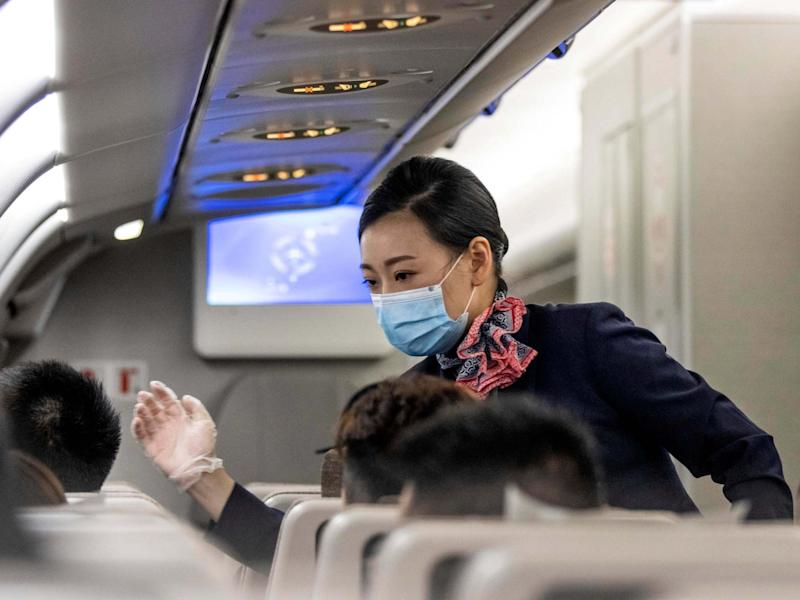 A flight attendant measures passengers temperature amid flight in the airplane bounded from Shanghai to Guangzhou, China, 18 June 2020: Alex Plavevski/EPA