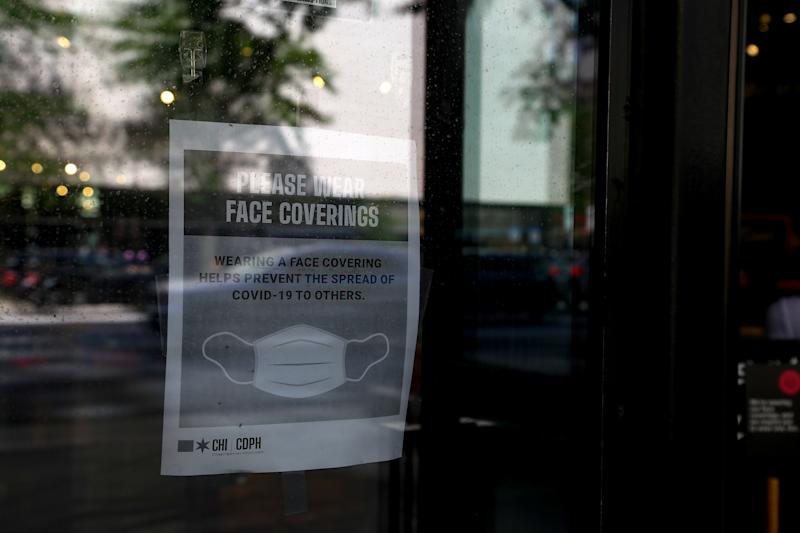 """A sign on the door of a shop in Chicago reads, """"Please wear face coverings. Wearing a face covering helps prevent the spread of COVID-19 to others."""""""