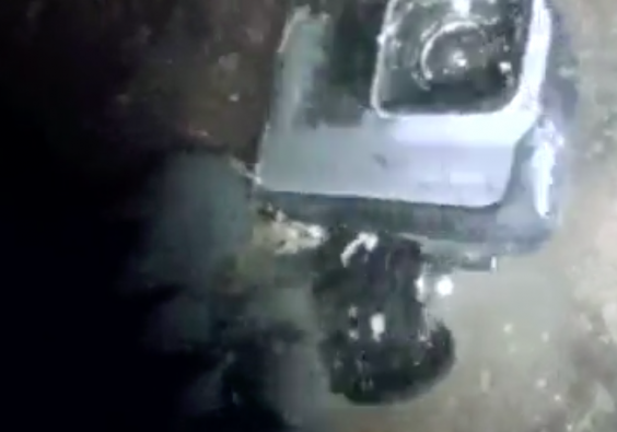 The GoPro spotted on the floor of a waterfall pool