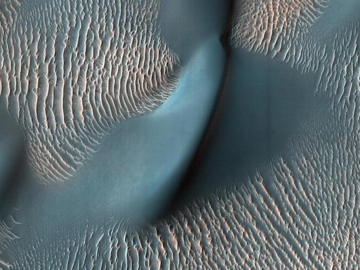 "The High Resolution Imaging Science Experiment (HiRISE) camera on NASA's Mars Reconnaissance Orbiter captured these sand ripples and large dune on February 9, 2009. Blue color has been added to make textures easier to see. <p class=""copyright"">NASA/JPL-Caltech/University of Arizona</p>"