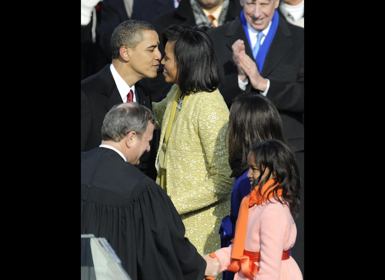 Barack Obama kisses his wife Michelle before daughters Sasha (R) and Malia (2nd-R) after Obama was sworn in as the 44th US president by Supreme Court Chief Justice John Roberts (L) at the US Capitol in Washington on January 20, 2009. AFP PHOTO / TIMOTHY A. CLARY (Photo credit should read TIMOTHY A. CLARY/AFP/Getty Images)