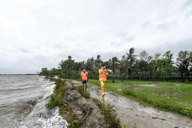 """Volunteers of the Cyclone Preparedness Programme (CPP) walk along in an alley as they use a megaphone to urge residents to evacuate to shelters ahead of the expected landfall of cyclone Amphan, in Dacope of Khulna district on May 20, 2020. - Several million people were taking shelter and praying for the best on Wednesday as the Bay of Bengal's fiercest cyclone in decades roared towards Bangladesh and eastern India, with forecasts of a potentially devastating and deadly storm surge. Authorities have scrambled to evacuate low lying areas in the path of Amphan, which is only the second """"super cyclone"""" to form in the northeastern Indian Ocean since records began. (Photo by Munir uz Zaman / AFP) (Photo by MUNIR UZ ZAMAN/AFP via Getty Images)"""