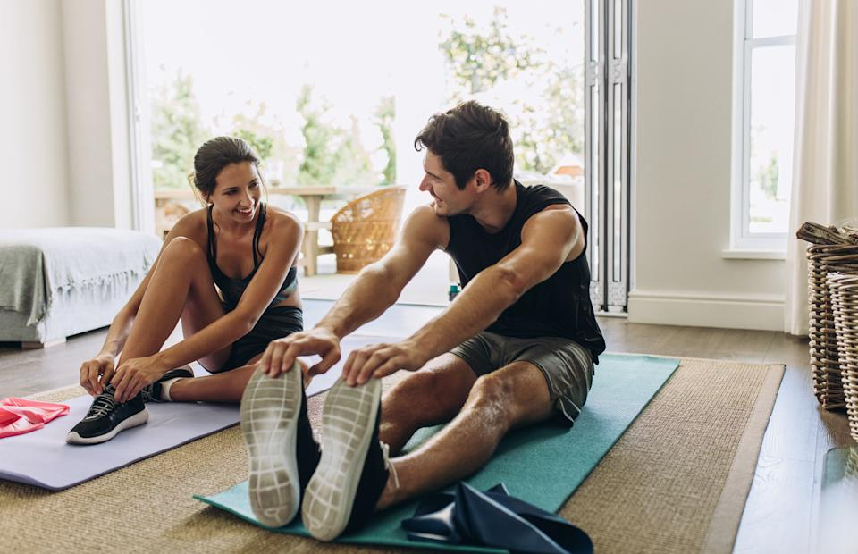 A young couple exercising together on yoga mats in their living room.