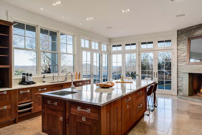 The kitchen has a working fireplace and stunning views of the surrounding woodlands.