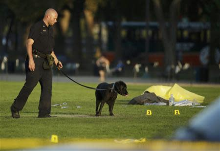 A law enforcement officer uses a police dog to search for evidence at the scene where a man set himself on fire within sight of the U.S. Capitol building on the U.S. National Mall in Washington, October 4, 2013. REUTERS/Gary Cameron