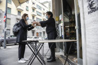 Bar owner Franco Epifani delivers cappuccino to a customer outside his bistrot bar, at Isola district, in Milan, Italy, Friday, Nov. 6, 2020. Lombardy is among the four Italian regions classified as red zones, where a strict lockdown will be imposed and reassessed in two weeks to curb the infections growing curve. (AP Photo/Luca Bruno)