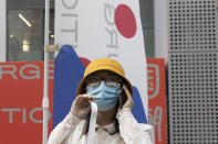 A woman wears a mask to prevent the spread of the coronavirus as she visits a weekend open air market in Beijing on Saturday, Aug. 8, 2020. As the coronavirus outbreak comes under control in the Chinese capital, normal life is slowing returning albeit with the requisite masks. (AP Photo/Ng Han Guan)